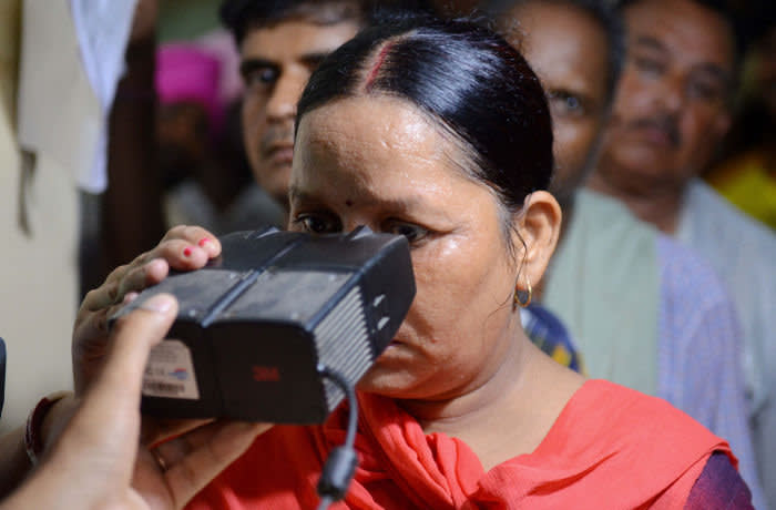 This photo taken on July 17, 2018 shows an Indian woman looking through an optical biometric reader that which scans an individual's iris patterns, during registration for Aadhaar cards (or unique identifier [UID] cards) in Amritsar. - India's top court on September 26 upheld the government's Aadhaar scheme, the world's largest biometric database, but imposed new restrictions on how the personal details of more than one billions citizens in the system can be used. (Photo by NARINDER NANU / AFP) (Photo credit should read NARINDER NANU/AFP via Getty Images)