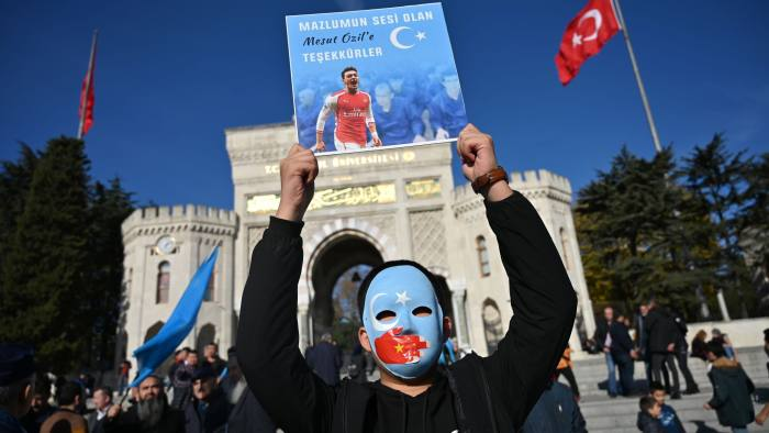 "(FILES) In this file photo taken on December 14, 2019 a supporter of China's Muslim Uighur minority holds a placard of Arsenal's Turkish origin German midfielder Mesut Ozil reading ""Thanks for being our voice"" during a demonstration at Beyazid square in Istanbul. - US Secretary of State Mike Pompeo on December 17, 2019 denounced China for its heavy-handed actions against Arsenal over footballer Mesut Ozil's support for incarcerated Uighurs, saying Beijing could not hide reality. Arsenal distanced itself from Ozil but Beijing dropped state television broadcasts of the English Premier League club's Sunday match -- a move that could have major commercial ramifications in the lucrative Chinese market. (Photo by Ozan KOSE / AFP) (Photo by OZAN KOSE/AFP via Getty Images)"