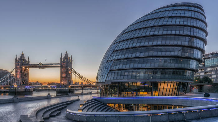 Photo taken by the side of Thames River before the sunrise with no people, showing the City Hall of London and Tower Bridge