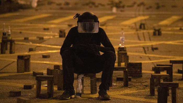 A protester sit with brick obstacles and Molotov cocktail on a barricade road near the the Hong Kong Polytechnic University campus in Hong Kong on Thursday, Nov. 14, 2019. Hong Kong police warned protesters on Thursday that they were moving