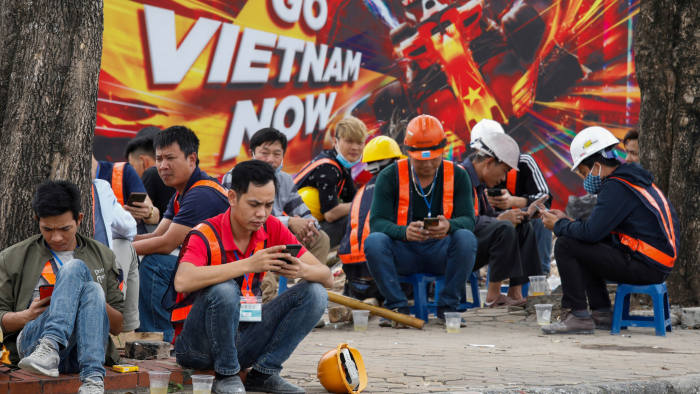 FILE PHOTO: Workers take a lunch break in front of a poster promoting Formula One Vietnam Grand Prix at the construction site of its racing track in Hanoi, Vietnam March 12, 2020. REUTERS/Kham/File Photo