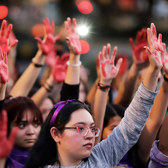 Women raise their hands as they protest against gender violence and femicide in Puebla, Mexico, February 22, 2020. REUTERS/Imelda Medina