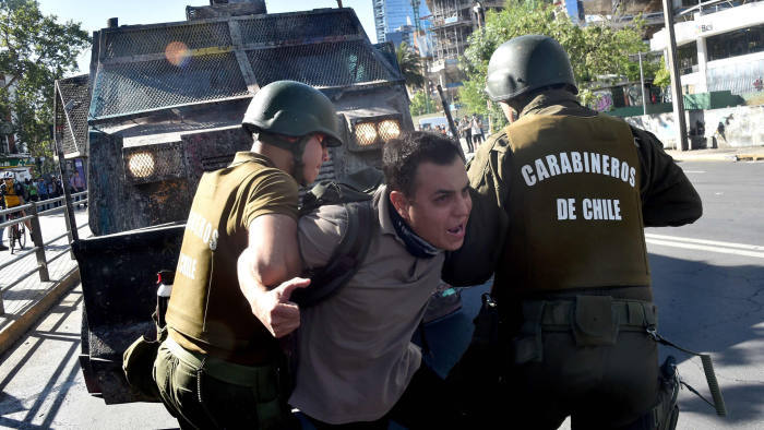 TOPSHOT - A demonstrator is detained by riot police during clashes in Santiago, on November 7, 2019. - Unrest began in Chile last October 18 with protests against a rise in transport tickets and other austerity measures that descended into vandalism, looting, and clashes between demonstrators and police. (Photo by Rodrigo ARANGUA / AFP) (Photo by RODRIGO ARANGUA/AFP via Getty Images)
