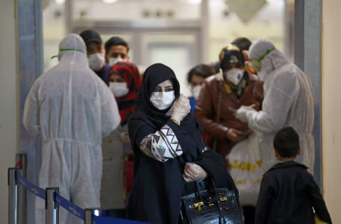 TOPSHOT - Medical staff in protective gears distribute information sheets to Iraqi passengers returning from Iran at Najaf International Airport on March 5, 2020. - Iraqi health authorities announced the country's first two deaths from the new coronavirus, one in the capital Baghdad and the other in the autonomous Kurdish region. (Photo by Haidar HAMDANI / AFP) (Photo by HAIDAR HAMDANI/AFP via Getty Images)