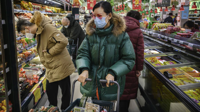 A woman wears a protective mask and sunglasses as she shops for groceries at a supermarket during the Chinese New Year and Spring Festival holiday in Beijing