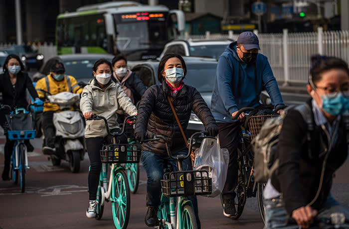 People wearing facemasks amid the concerns over the COVID-19 coronavirus commute on a street in Beijing on April 7, 2020. (Photo by NICOLAS ASFOURI / AFP) (Photo by NICOLAS ASFOURI/AFP via Getty Images)