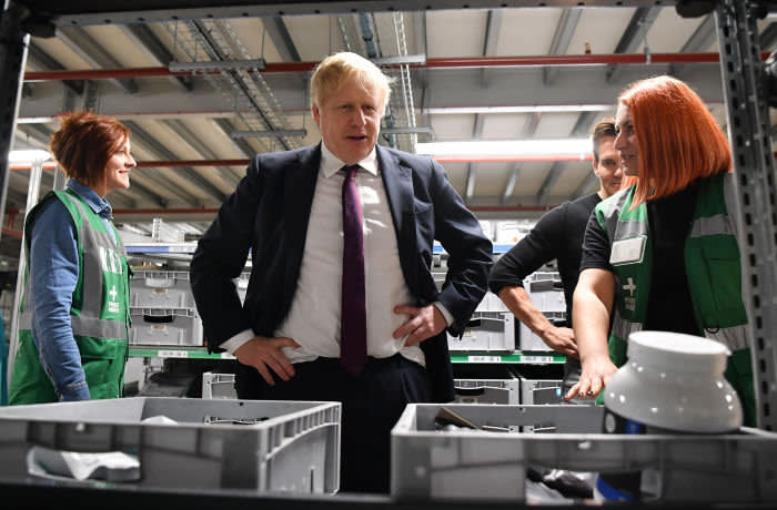 Britain's Prime Minister and Conservative party leader Boris Johnson (C) speaks with staff members in a fulfilment centre for The Hut Group (THG) in Warrington, in north-west England on December 10, 2019, as campaigning in the general election enters it's final days. - Britain will go to the polls on December 12, 2019 to vote in a pre-Christmas general election. (Photo by Ben STANSALL / POOL / AFP) (Photo by BEN STANSALL/POOL/AFP via Getty Images)