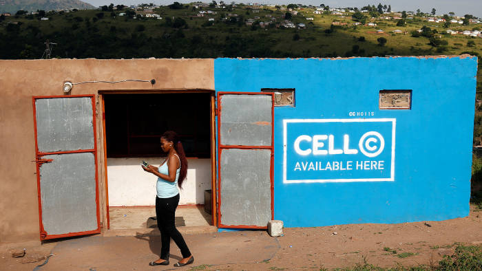 A woman uses her mobile phone in front of a store with telecom company Cell C branding in Kwandengezi, South Africa March 28, 2017. REUTERS/Rogan Ward - RC15FD457D40