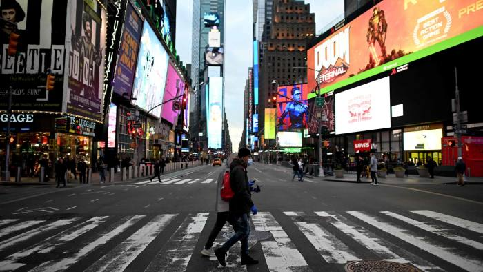 People wearing masks cross the street in Times Square in Manhattan on March 17, 2020 in New York City. - The coronavirus outbreak has transformed the US virtually overnight from a place of boundless consumerism to one suddenly constrained by nesting and social distancing. (Photo by Johannes EISELE / AFP) (Photo by JOHANNES EISELE/AFP via Getty Images)