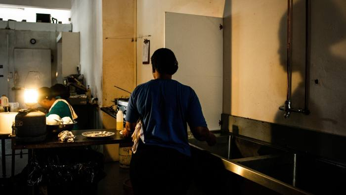 Workers in a cafe use an emergency gas-powered lamp to illuminate the kitchen after a load-shedding power outage stopped their electricity supply in Johannesburg, South Africa, on Thursday, Feb. 14, 2019. Eskom Holdings SOC Ltd. cut supplies for the fifth day on Thursday and warned its power generation system remains