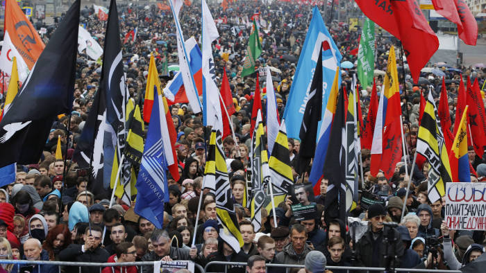 People hold various banners and flags during a rally to support political prisoners in Moscow, Russia, Sunday, Sept. 29, 2019. (AP Photo/Dmitri Lovetsky)