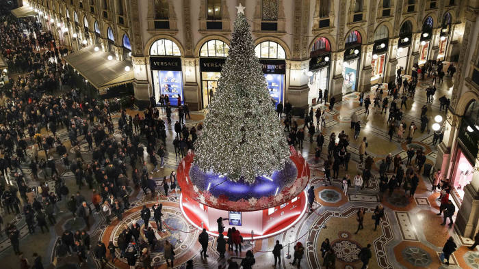 Shoppers crowd Milan's Victor Emmanuel II arcade in northern Italy, where a giant Christmas tree and lights are set up, Tuesday, Dec. 10, 2019. (AP Photo/Luca Bruno)