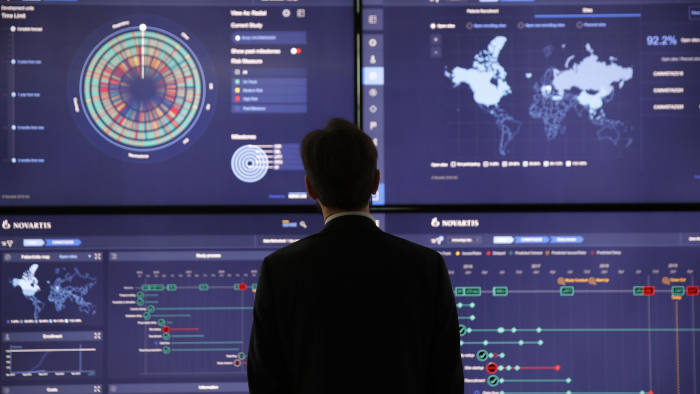 An employee looks at data on screens in the high-tech command center at the Novartis AG campus in Basel, Switzerland, on Wednesday, Jan. 16, 2019. Trying to streamline an operation that spends more than $5 billion a year on developing new drugs, Novartis dispatched teams to jetmaker Boeing Co. and Swissgrid AG, a power company, to observe how they use technology-laden crisis centers to prevent failures and blackouts. Photographer: Stefan Wermuth/Bloomberg