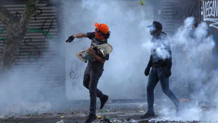 SANTIAGO, CHILE - OCTOBER 20: Anti-government demonstrators clash with police as they protest against cost of living increases on October 20, 2019 in Santiago, Chile. President Sebastian Piñera suspended the 3.5% subway fare hike and declared the state of emergency for the first time since the return of democracy in 1990. Protests had begun on Friday and developed into looting and arson, generating chaos in Santiago, Valparaiso and a dozen of other cities. (Photo by Marcelo Hernandez/Getty Images) ***BESTPIX***