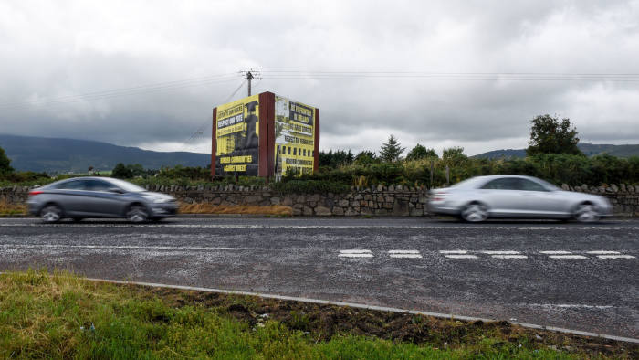 Automobiles pass a poster reading 'No EU Frontier in Ireland, No hard Border, Respect the remain vote' erected by campaign group Border Communities Against Brexit, in Killeen, Northern Ireland, on Friday, July 20, 2018. How to keep the Irish border open after the U.K. leaves the European Union hasbecomethe trickiest issue in Brexit negotiations. Photographer: Mary Turner/Bloomberg