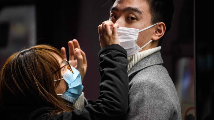 A couple wearing face masks wait on a MTR underground metro train platform during a Lunar New Year of the Rat public holiday in Hong Kong on January 27, 2020, as a preventative measure following a coronavirus outbreak which began in the Chinese city of Wuhan. (Photo by Anthony WALLACE / AFP) (Photo by ANTHONY WALLACE/AFP via Getty Images)