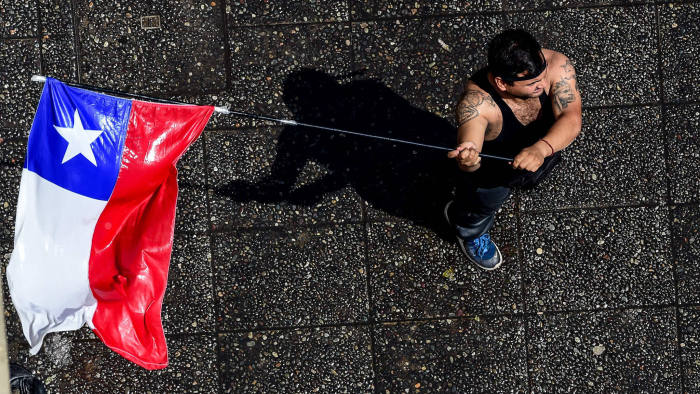 TOPSHOT - A demonstrator waves the Chilean national flag during a protest in Santiago, on October 20, 2019. - Fresh clashes broke out in Chile's capital Santiago on Sunday after two people died when a supermarket was torched overnight as violent protests sparked by anger over economic conditions and social inequality raged into a third day. (Photo by MARTIN BERNETTI / AFP) (Photo by MARTIN BERNETTI/AFP via Getty Images)