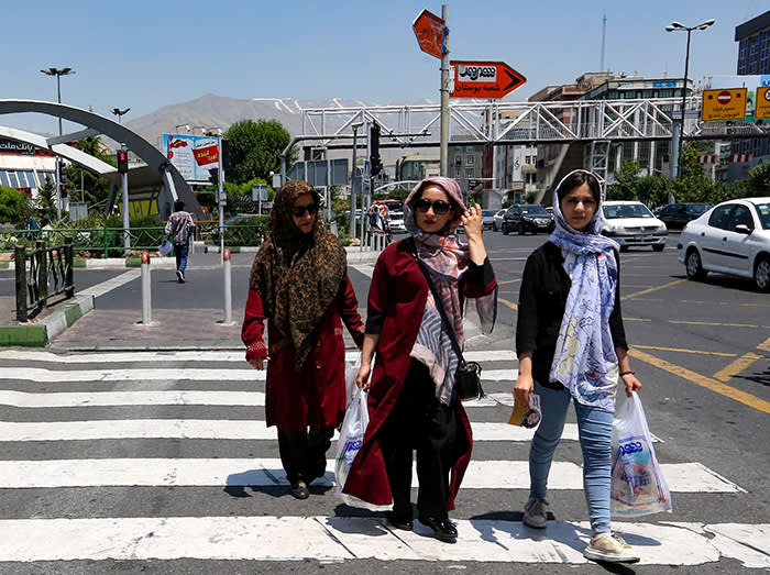 Iranian women carry their shopping bags as they cross a road in the Iranian capital Tehran on June 15, 2019. - US President Donald Trump last year withdrew from the 2015 nuclear deal with Iran and imposed tough sanctions on the Islamic Republic. (Photo by ATTA KENARE / AFP) (Photo credit should read ATTA KENARE/AFP via Getty Images)