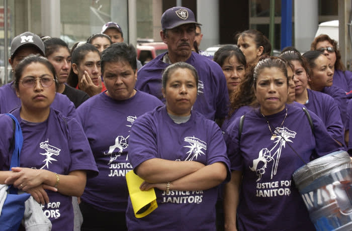 Members of Justice for Janitors gather in a lot at the corner of 17th and Welton for a rally before the group began their march through downtown. Hundreds of Denver janitors with family and community supporters rallied in downtown Denver to urge employers to provide affordable health care and better wages. Lead by Justice for Janitors the group stopped at a number of downtown buildings including Republic Plaza. (05/22/03)(Craig F. Walker/The Denver Post) (Photo By Craig F. Walker/The Denver Post via Getty Images)