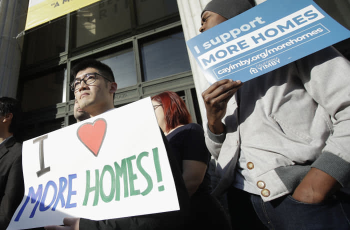 FILE - In this Jan. 7, 2020, file photo, men hold up signs at a rally outside of City Hall in Oakland, Calif. California's Gov. Gavin Newsom said Wednesday, Jan. 8, 2020, that he is seeking $750 million to help pay rent for people facing homelessness, among other purposes, in the most populous state's latest attempt to fight what he called a national crisis. (AP Photo/Jeff Chiu, File)