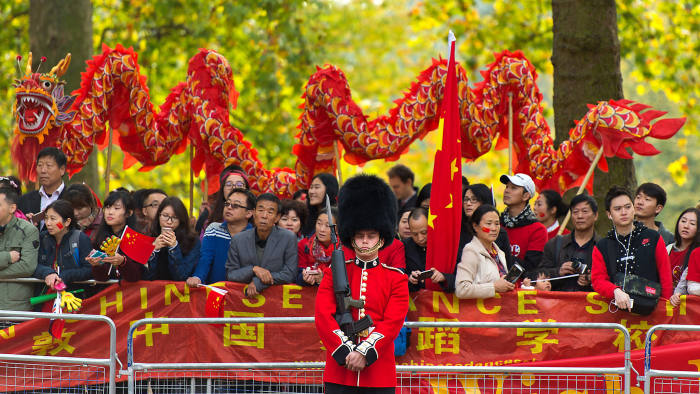 LONDON, ENGLAND - OCTOBER 20: Pro-China supporters perform a dragon dance behind a Queen's Guard during a state visit by Chinese President Xi Jinping on October 20, 2015 in London, England. The President of the People's Republic of China, Mr Xi Jinping and his wife, Madame Peng Liyuan, are paying a State Visit to the United Kingdom as guests of The Queen. They will stay at Buckingham Palace and undertake engagements in London and Manchester. The last state visit paid by a Chinese President to the UK was Hu Jintao in 2005. (Photo by Ben Pruchnie/Getty Images)