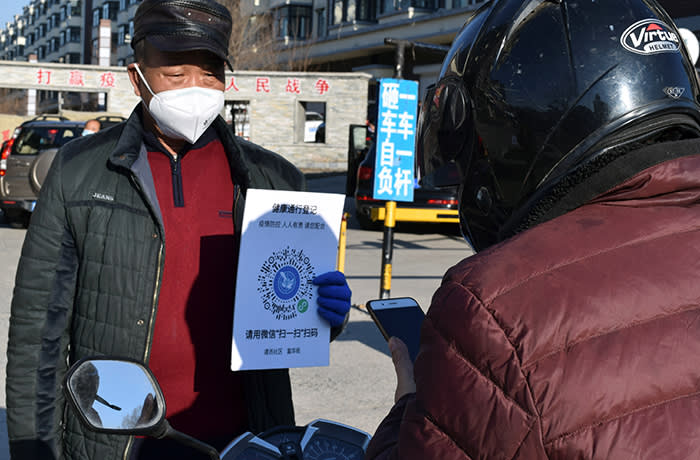 A volunteer holds a sign with a QR code to indicate health status at an entrance to a residential compound following an outbreak of the coronavirus disease (COVID-19), in Suifenhe, a city bordering Russia in China's Heilongjiang province, April 15, 2020. REUTERS/Huizhong Wu - RC225G90XNHI
