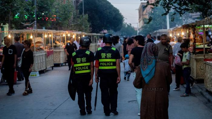 "This picture taken on June 25, 2017 shows police patrolling in a night food market near the Id Kah Mosque in Kashgar in China's Xinjiang Uighur Autonomous Region, a day before the Eid al-Fitr holiday. - Xinjiang has seen an explosion in the construction of vocational training"" centers for the region's Muslim minorities. But the centers have come under international scrutiny, with rights activists describing them as political re-education camps holding as many as one million ethnic Uighurs and other Muslim minorities. (Photo by Johannes EISELE / AFP) / TO GO WITH China-politics-rights-Xinjiang, FOCUS by Ben Dooley (Photo credit should read JOHANNES EISELE/AFP via Getty Images)"