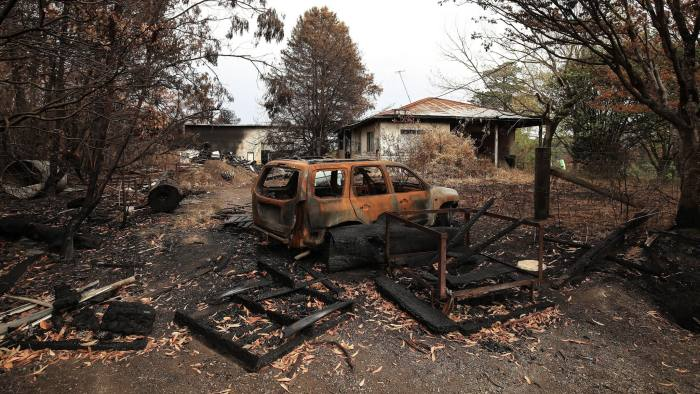 A burnt out vehicle outside a damaged home in Bilpin, New South Wales, Australia, on Tuesday. The bushfires have forced tens of thousands of people to evacuate the states of New South Wales and Victoria.