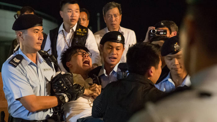epa06258405 YEARENDER 2017 JUNE Demosisto secretary general Joshua Wong is arrested by police after climbing on the Golden Bauhinia statue during a protest in Golden Bauhinia Square in Hong Kong, China, 28 June 2017. The Golden Bauhinia Statue was a present from the Chinese government celebrating the return of Hong Kong to mainland China in 1997. The protest took place next to the Convention Centre ahead of Chinese President Xi Jinping's visit where he will inaugurate a new Hong Kong Chief Executive and to mark the 20th anniversary of the city's handover from British to Chinese rule on 01 July. EPA/ROMAN PILIPEY