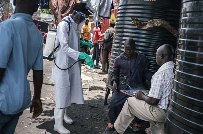A staff member of Kenya's Ministry of Health sprays disinfectant on a game board to curb the spread of the COVID-19 coronavirus at the Gikomba Market in Nairobi, Kenya, on March 21, 2020. - African countries have been among the last to be hit by the global COVID-19 coronavirus epidemic but as cases rise, many nations are now taking strict measures to block the deadly illness. (Photo by Gordwin ODHIAMBO / AFP) (Photo by GORDWIN ODHIAMBO/AFP via Getty Images)