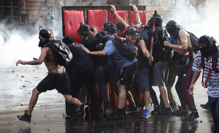 Demonstrators clash with riot police water cannon during a protest against the government in Santiago on November 28, 2019. - Furious Chileans have since October 18 been protesting social and economic inequality, and against an entrenched political elite that comes from a small number of the wealthiest families in the country, among other issues. (Photo by Johan ORDONEZ / AFP) (Photo by JOHAN ORDONEZ/AFP via Getty Images)