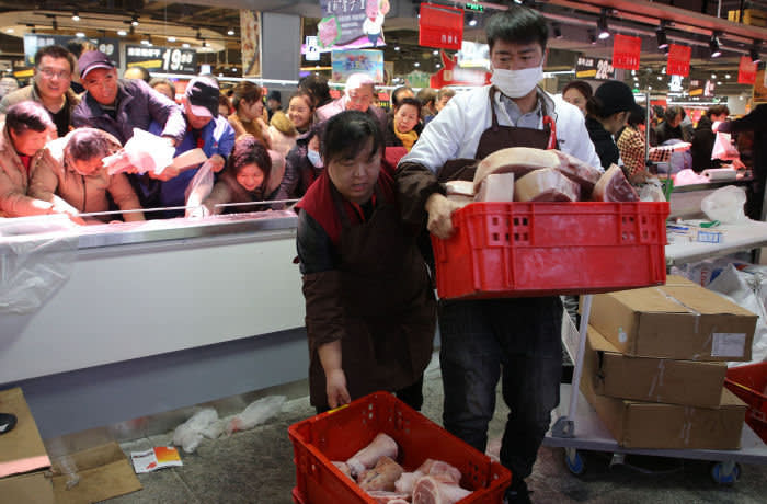 This photo taken on December 19, 2019 shows people trying to buy discounted pork at a newly-opened supermarket in Binzhou, in China's eastern Shandong Province. - The supermarket offered 3 tonnes of pork at discounted prices as a promotion. Pork prices in China have doubled this year following an outbreak of African swine fever. (Photo by STR / AFP) / China OUT (Photo by STR/AFP via Getty Images)