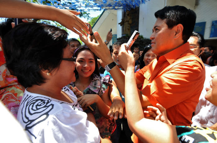 Presidential candidate and senator Manuel Villar (L) greets his supporters after attending a mass at a church in Las Pinas, south of Manila on May 9, 2010. More than 17,000 positions ranging from president to town councillors will be contested when the Philippines holds national elections on May 10. AFP PHOTO/NOEL CELIS (Photo credit should read NOEL CELIS/AFP via Getty Images)