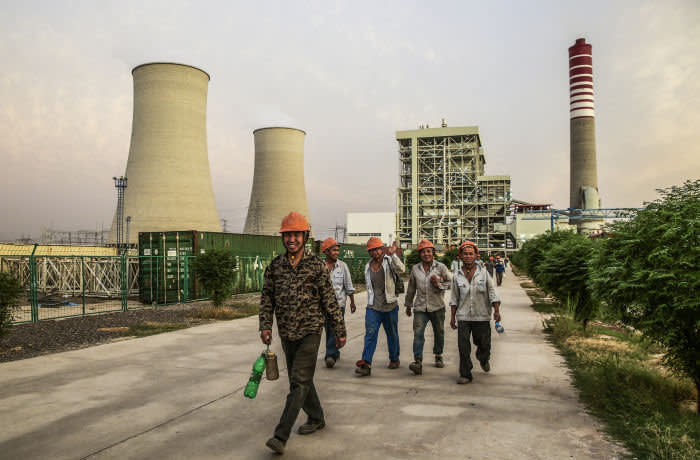 Chinese workers walk along a path at the Sahiwal coal power plant, owned by China's state-owned Huaneng Shandong Rui Group, in Sahiwal, Punjab, Pakistan, on Wednesday, June 14, 2017. Pakistan is racing to bridge its power supply gap before national elections next year after a series of widespread blackouts highlighted the fragility of the network and its negative pull on South Asia's second largest economy. Photographer: Asad Zaidi/Bloomberg