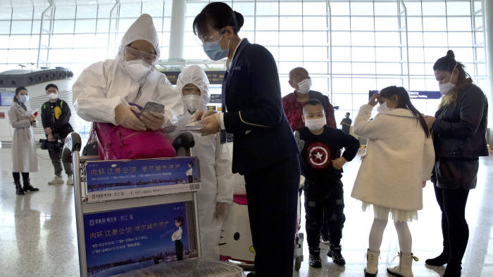 A worker assists travelers wearing face masks and suits to protect against the spread of new coronavirus at Wuhan Tianhe International Airport in Wuhan in central China's Hubei Province, Wednesday, April 8, 2020. Within hours of China lifting an 11-week lockdown on the central city of Wuhan early Wednesday, tens of thousands people had left the city by train and plane alone, according to local media reports. (AP Photo/Ng Han Guan)