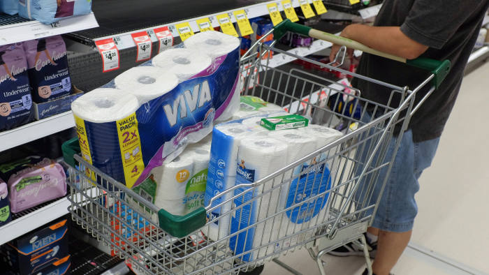 """A customer holds a shopping cart filled with toilet and kitchen paper at a supermarket in Sydney, Australia, on Wednesday, March 4, 2020. Australia's four biggest lenders have heeded the prime minister's plea to """"do their bit"""" to help the country weather the expected economic hit from the coronavirus, by passing on the central bank's latest interest-rate cut in full. Photographer: Brendon Thorne/Bloomberg"""