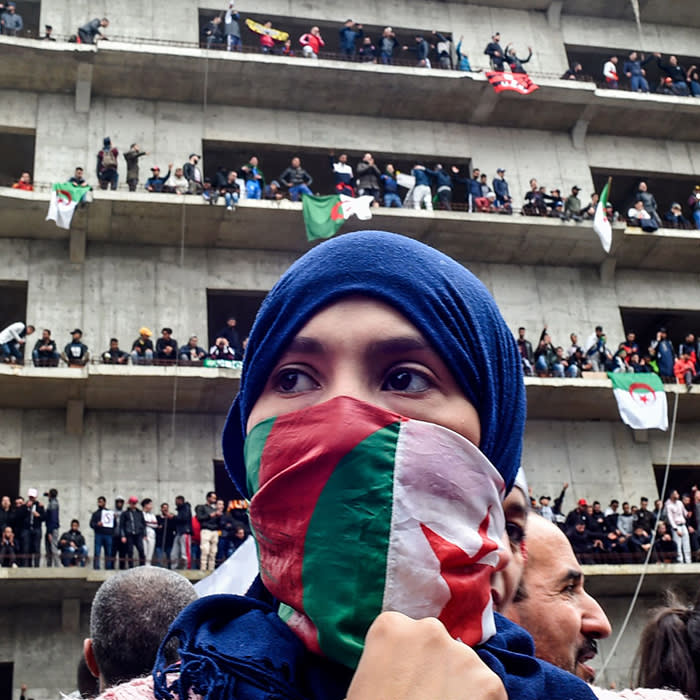 """ALGERIA - AFP PICTURES OF THE YEAR 2019 - A woman covers her face with the national flag, as Algerian protesters demonstrate in the capital Algiers against ailing president's bid for a fifth term on March 8, 2019. - Tens of thousands protested across Algeria today in the biggest rallies yet against ailing President Abdelaziz Bouteflika's bid for a fifth term, despite the defiant leader's warning of the risk of """"chaos"""". (Photo by RYAD KRAMDI / AFP) (Photo by RYAD KRAMDI/AFP via Getty Images)"""