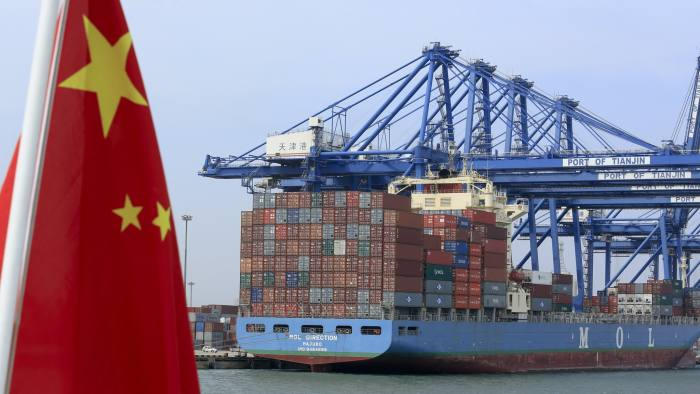 A Chinese flag flies on a vessel moving past shipping containers being unloaded at a Tianjin Port (Group) Co. Ltd. dock in Tianjin, China, on Wednesday, Sept. 12, 2012. The Chinese government is trying to meet a 7.5 percent economic growth target set in March, which would already be the weakest expansion since 1990. Photographer: Nelson Ching/Bloomberg