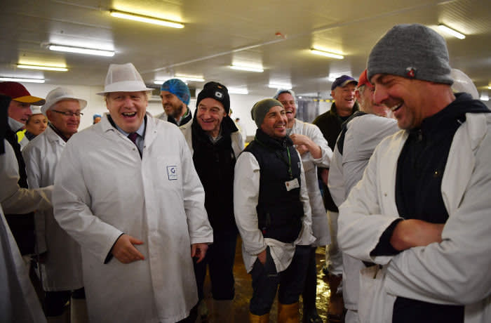 Britain's Prime Minister and Conservative leader Boris Johnson (L) talks with traders during a general election campagin visit to Grimsby Fish Market in Grimsby, northeast England, on December 9, 2019. - Britain will go to the polls on December 12, 2019 to vote in a pre-Christmas general election. (Photo by Ben STANSALL / various sources / AFP) (Photo by BEN STANSALL/AFP via Getty Images)