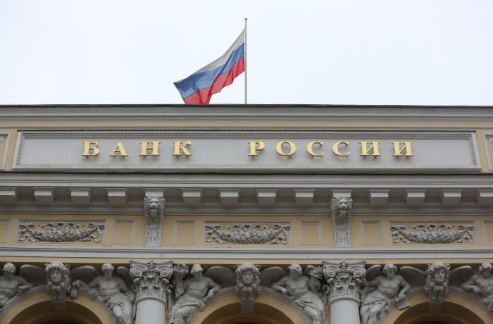 A Russian national flag flies above the headquarters of Bank Rossii, Russia's central bank, ahead of a news conference to announce interest rates in Moscow, Russia, on Friday, Dec. 15, 2017. Russia's central bank unexpectedly accelerated its pace of monetary easing with this year's third cut of a half point after price growth fell to a record and a deal between OPEC and its allies to maintain oil production cuts until the end of 2018. Photographer: Andrey Rudakov/Bloomberg