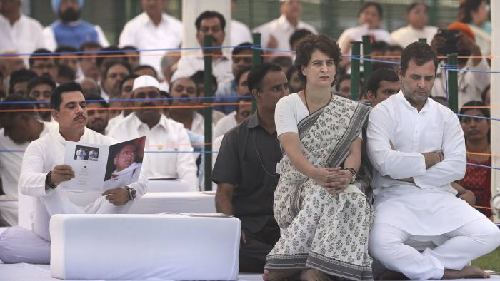 Congress Party President Rahul Gandhi, right, with his sister and party general secretary Priyanka Gandhi Vadra, second right, sit as her husband Robert Vadra, left, reads a booklet on Rajiv Gandhi during a function to pay homage to former Indian prime minister Rajiv Gandhi on his death anniversary in New Delhi, India, Tuesday, May 21, 2019. Gandhi was assassinated during national elections by a suicide bomber in 1991. (AP Photo/Manish Swarup)