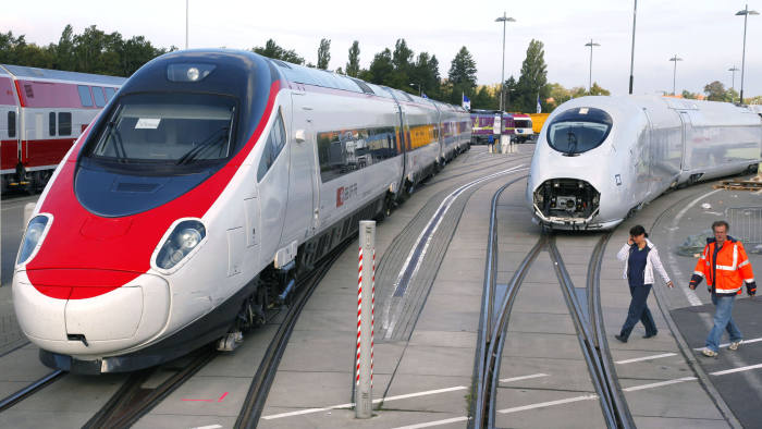 FILE: Workers walk past an Alstom SA Pendolino high-speed train, left, and a Siemens AG Velaro high-speed train as they sit on display prior to the opening of the InnoTrans International Trade Fair on Transport Technology in Berlin, Germany, on Saturday, Sept. 18, 2010. Siemens AG and Alstom SA are nearing an agreement on a framework to tie up their rail units that seeks to create a European transportation giant. A tie-up of the two assets would create the world's second-largest maker of rail cars and locomotives after China's CRRC Corp., giving Siemens and Alstom more heft to confront growing competition from China. Our editors select the best archive images from the two companies. Photographer: Jochen Eckel/Bloomberg
