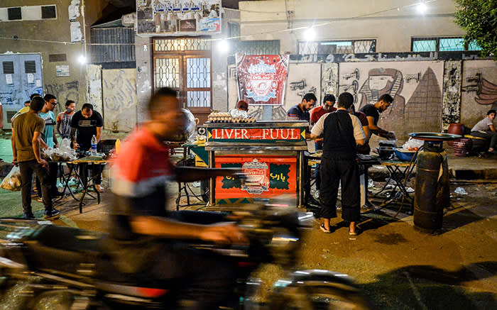 """Egyptians order food during the pre-dawn 'suhur' meal before a new day of fasting begins, early on May 31, 2019, from a food cart by the name """"Liver Fuul"""", a play on Arabic name for fava beans and English football club Liverpool FC, in the Ain Shams suburb of northeastern Cairo. - Egyptian football fans readied to cheer on national hero Mohamed Salah in Sunday's Champions League clash and tuck into food from a cart whose owner vows they'll """"never eat alone"""". A tribute to the Reds, the """"Liverfuul"""" cart serves up hot dishes of """"fuul"""" (fava beans) in Ain Shams, a working-class suburb of Cairo. (Photo by Ahmed HASAN / AFP) (Photo credit should read AHMED HASAN/AFP via Getty Images)"""