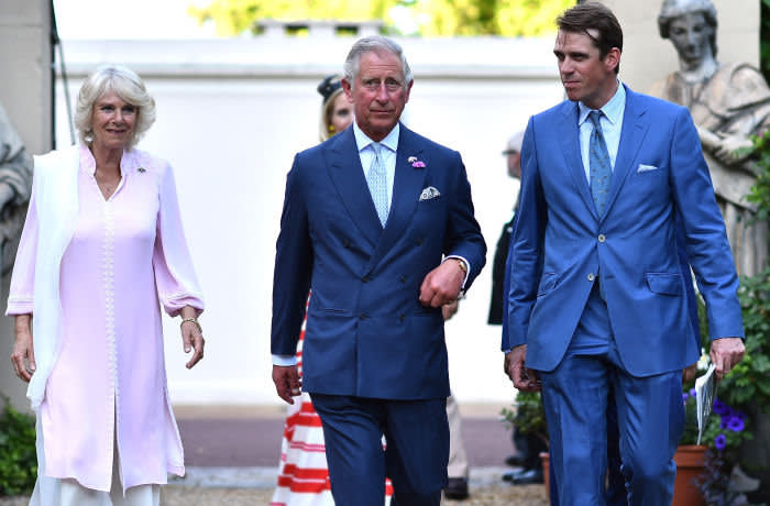 ***Retouched to defocus lady in red in background (L-R) Britain's Camilla, Duchess of Cornwall, Britain's Prince Charles, Prince of Wales and Ben Elliot arive for a reception in support of the Elephant family, a charity set up by Mark Shand, the Duchess of Cornwall's brother in London on June 30. 2015. The event called Travels to my Elephant will see painted rickshaws auctioned to raise money for Asian Elephants and later this year taking part in a race across Madhya Pradesh in India. AFP PHOTO / BEN STANSALL (Photo by BEN STANSALL / AFP)