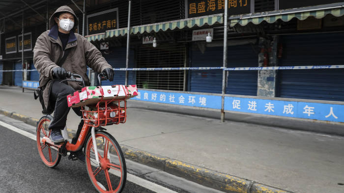 WUHAN, CHINA - JANUARY 17: (CHINA OUT) A man wears a mask while riding on mobike past the closed Huanan Seafood Wholesale Market, which has been linked to cases of Coronavirus, on January 17, 2020 in Wuhan, Hubei province, China. Local authorities have confirmed that a second person in the city has died of a pneumonia-like virus since the outbreak started in December. (Photo by Getty Images)