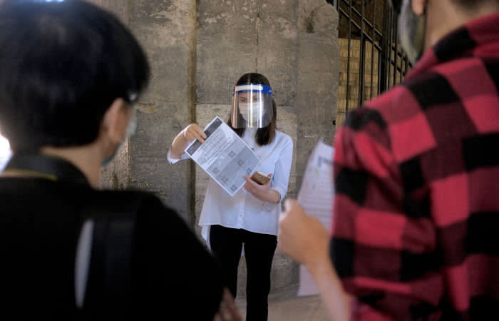 ROME, ITALY - JUNE 01: People watch a tourist guide,wearing a face shield, as they visit in the Colosseum, after three months of closure due to the COVID-19 lockdown measures on June 1, 2020 in Rome, Italy. The Parco archeologico del Colosseo and its monuments the Colosseum, Palatine, Roman Forum and Domus Aurea are opening to the public today, with access restrictions for visitors, as Italy relaxes Europe's strictest and longest-running coronavirus lockdown. (Photo by Simona Granati - Corbis/Corbis via Getty Images)
