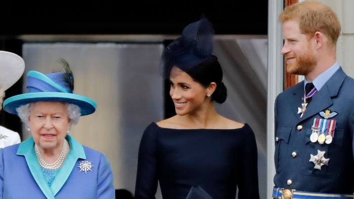 (FILES) In this file photo taken on July 10, 2018 (L-R) Britain's Queen Elizabeth II, Meghan, Duchess of Sussex, Britain's Prince Harry, Duke of Sussex stand on the balcony of Buckingham Palace in London to watch a military fly-past to mark the centenary of the Royal Air Force (RAF). - Britain's Queen Elizabeth II on January 13, 2020, said Prince Harry and his wife Meghan would be allowed to split their time between Britain and Canada while their future is finalised. The couple said last week they wanted to step back from the royal frontline, catching the family off guard and forcing the monarch to convene crisis talks about the pair's future roles. (Photo by Tolga AKMEN / AFP) (Photo by TOLGA AKMEN/AFP via Getty Images)
