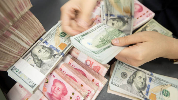 (FILES) In this file photo taken on August 5, 2019 a Chinese bank employee counts 100-yuan notes and US dollar bills at a bank counter in Nantong in China's eastern Jiangsu province. - The United States on January 13, 2020 will formally retract its accusation that China manipulates its currency to gain unfair trade advantages, according to a media report.The news emerges two days before Beijing and Washington are due to sign a partial trade deal, marking an end to nearly two years of trade conflict.It would also undo the major escalation from August by President Donald Trump, who made good on a campaign pledge to brand Beijing a currency manipulator. (Photo by STR / AFP) / China OUT (Photo by STR/AFP via Getty Images)