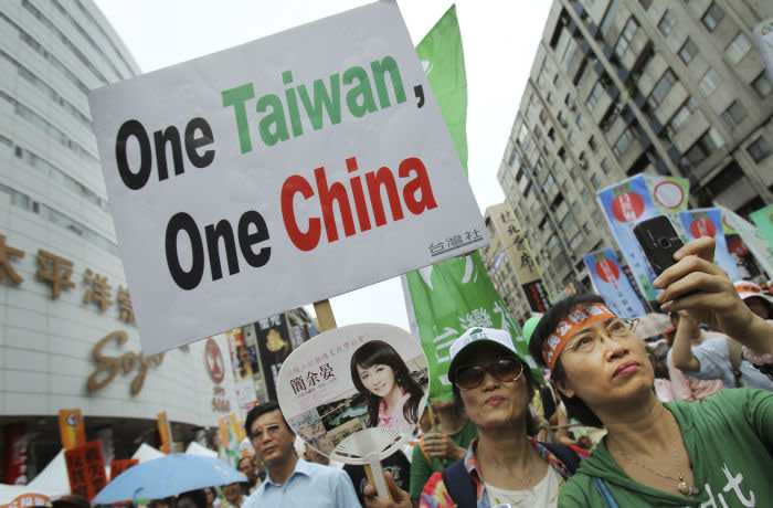 FILE - June 26, 2010, anti-China demonstrators hold placards as they march in a street, denouncing the Economic Cooperation Framework Agreement (ECFA) planned with China, in Taipei, Taiwan. (AP Photo/Wally Santana, File)