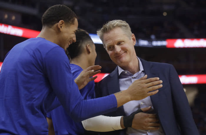 Golden State Warriors coach Steve Kerr, right, smiles with players during the second half of the team's preseason NBA basketball game against the Los Angeles Lakers in San Francisco, Saturday, Oct. 5, 2019. (AP Photo/Jeff Chiu)